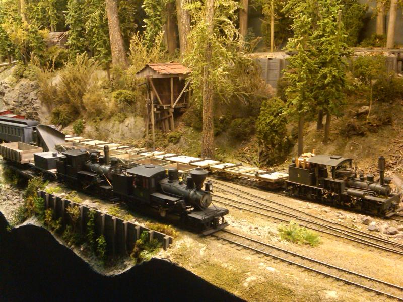 A shay and 2 climax locomotives hanging out in the yard